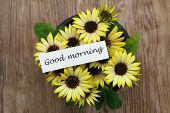 Good morning card with yellow daisies on wooden surface