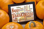 Happy Thanksgiving word cloud on a digital tablet surrounded by pumpkins