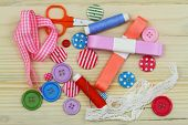 Colorful buttons, ribbon, thread, needles and scissors on wooden surface