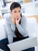 Lady sitting on sofa with concerned look on her face while on her laptop computer