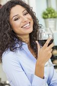 Beautiful young Latina Hispanic woman smiling, relaxing and drinking a glass of red wine