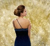 people, holidays, christmas, and glamour concept - smiling woman in evening dress over yellow lights