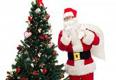 christmas, holidays and people concept - man in costume of santa claus with bag and christmas tree making hush gesture