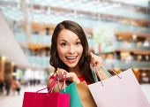 sale, gifts, holidays and people concept - smiling woman with colorful bags over shopping center bac