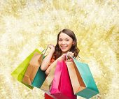 sale, gifts, christmas, holidays and people concept - smiling woman with colorful shopping bags over yellow lights background