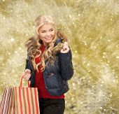 happiness, winter holidays, christmas and people concept - smiling young woman in winter clothes with shopping bags over yellow lights background