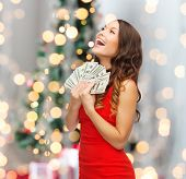 holidays, sale, banking and people concept - smiling woman in red dress with us dollar money over ch
