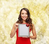 christmas, holidays, technology and people concept - smiling woman in red dress with tablet pc computer over yellow lights background