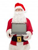 christmas, advertisement, technology, and people concept - man in costume of santa claus with laptop