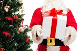 christmas, holidays and people concept - close up of santa claus with gift box and tree