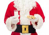 christmas, holidays, food, drink and people concept - close up of santa claus with glass of milk and