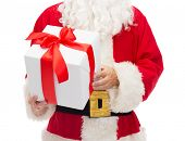 christmas, holidays and people concept - close up of santa claus with gift box