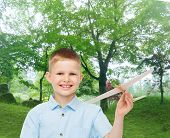 dreams, future, hobby, nature and childhood concept - smiling little boy holding wooden airplane model in his hand over park background