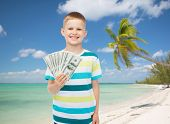 financial, summer, childhood and travel concept - smiling boy holding dollar cash money in his hand