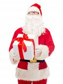 christmas, holidays and people concept - man in costume of santa claus with gift box
