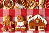 Christmas homemade gingerbread couple and house on tablecloth