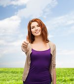 nature, summer, gesture and people concept - smiling teenage girl in casual clothes showing thumbs u