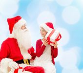 holidays, christmas, childhood and people concept - smiling little girl with santa claus and gifts o