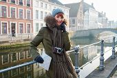 Woman tourist along canal in Bruges, Belgium