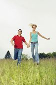Couple running in meadow