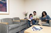 Family reading magazines in waiting room
