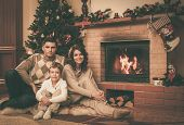 Family near fireplace in Christmas decorated house interior
