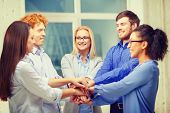 business, office, gesture and startup concept - smiling creative team with hands on top of each othe
