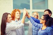 business, office, gesture and startup concept - smiling creative team doing high five gesture in office