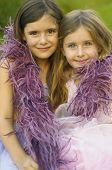 Two young girls wearing feather boa and smiling