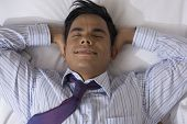 Hispanic businessman laying on bed
