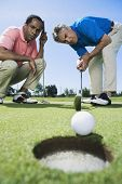 Multi-ethnic men looking at golf ball