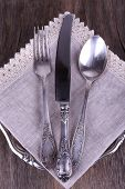 Metal knife, spoon and fork on lace napkin on metal plate on wooden background