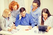 business, office, technology and startup concept - creative team with papers and clipboard working a