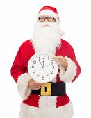 christmas, holidays and people concept - man in costume of santa claus with clock showing twelve poi