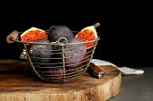 Ripe sweet figs in metal basket, on wooden table, on dark background