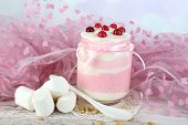 Raspberry milk dessert in glass jar, on color wooden  table, on light background