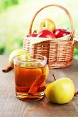 Apple cider in glass  with cinnamon sticks and fresh apples in wicker basket on wooden table, on bri