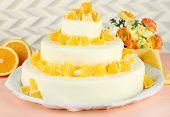 Beautiful wedding cake with oranges on  light background