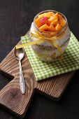 Healthy breakfast - yogurt with  fresh peach and muesli served in glass jar, on wooden background
