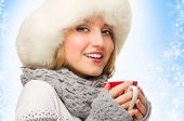 Young girl with mug on blue winter background