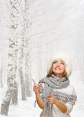 Young girl shows pointing gesture at winter forest