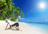 Businessman working with laptop on beach.