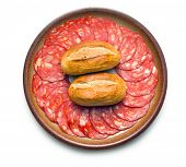 sliced chorizo salami with buns on plate