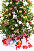 Presents under Christmas tree isolated on white