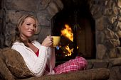 Woman With Tea Sitting By Fireplace