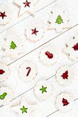 stock photo of linzer  - Overhead view of Christmas linzer cookies with Jam arranged on a white wooden background - JPG