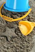 Spade and bucket  on sandy beach background