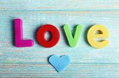Love word formed with colorful letters on wooden background