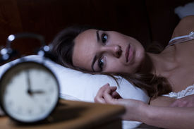 stock photo of suffering  - Woman lying in bed suffering from insomnia - JPG