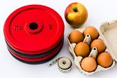 Weight Plates, Eggs, Apple And Measuring Tape. Fitness And Nutrition